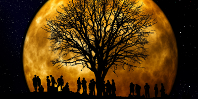 People by tree silhouette in front of full moon