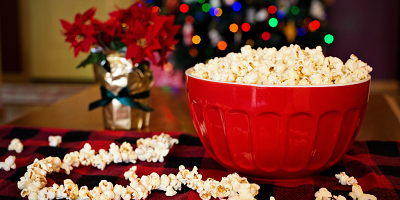 Bowl of popcorn in front of poinsettia and holiday lights