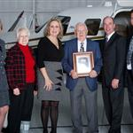 2012 Quality of Life Award Winners holding their placard beside a propeller driven airplane